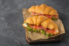 Close up of delicious home made croissants with smoked salmon o. Close up of delicious home made croissants with smocked salmon on a black background. Tasty royalty free stock photography