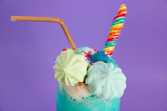 Close up of a delicious homemade extreme milkshake with dragees over a milk foam and a rainbow candy on top with a Royalty Free Stock Image