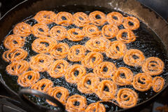 Close-up of delicious jalebis. Frying in oil pan at stall Stock Photography