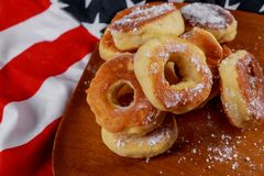 Close up of delicious lush donuts with top over american flag background. American independence day, celebration, patriotism and holidays concept stock image