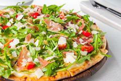 Close up Delicious Pizza with hamon and cherry tomato slices, parmezan cheese and arugula on the wooden board on t Royalty Free Stock Image