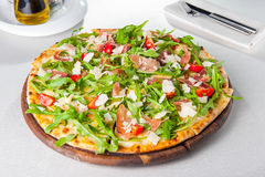Close up Delicious Pizza with hamon and cherry tomato slices, parmezan cheese and arugula on the wooden board on t Royalty Free Stock Photo