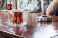 Close up of delicious red Turkish tea with traditional authentic glass with a teaspoon and ashtray on a table. Close up of delicious red Turkish tea with Stock Photos