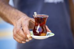 Delicious red Turkish tea with traditional pear shaped glass with a teaspoon in the man hand. Close-up of delicious red Turkish tea with traditional pear shaped Stock Photos