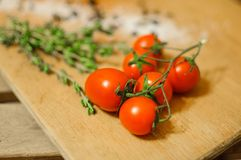 Cherry tomatoes, salt and herbs on wooden board. Close up delicious ripe cherry tomatoes, salt and rosemary on wooden cutting board Royalty Free Stock Image