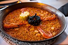 Close-up of delicious seafood valencia paella with king prawns, rice with spices and lemon wedges in pan, view from above Royalty Free Stock Photos