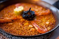 Close-up of delicious seafood valencia paella with king prawns, rice with spices and lemon wedges in pan, view from royalty free stock photo