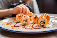 Food photographer takes picure of sushi rolls. Close up delicious sushi rolls on plate with blurred photographer in background Royalty Free Stock Photography