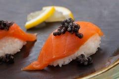 Nigiri Sushi with Fresh Salmon and Black Caviar. Close up of delicious two pieces Nigiri sushi with fresh salmon and black caviar. Elite food Stock Image