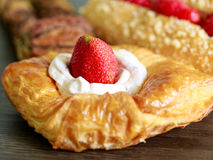 Close up delicius strawberry danish pastry and a cup of hot tea. Close up delicius strawberry danish pastry on the wood table Royalty Free Stock Images