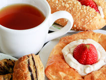 Close up delicius strawberry danish pastry and a cup of hot tea. Close up delicius strawberry danish pastry on the wood table Stock Image