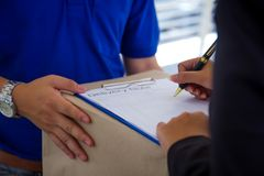 Close up Delivery man in blue uniform holding package while woman is signing receiving documents. stock photo