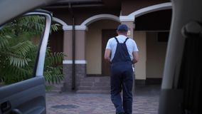 Worker of delivery service carrying coffee to door. Close-up of delivery man taking cups with coffee out of van and walking to house door. Adult food delivery stock footage