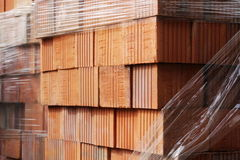 Close up delivery of red bricks for construction of new home by builders Stock Photography