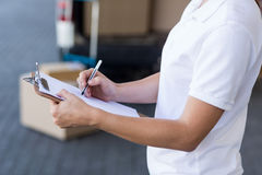 Close up of delivery woman is writing on a clipboard Stock Photo