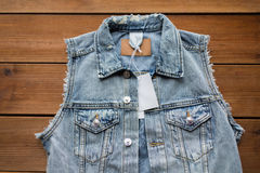 Close up of denim waistcoat with price tag on wood Royalty Free Stock Photography