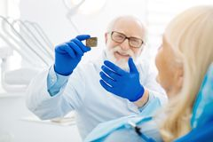 Close up of dental Xray image. Nothing serious detected. Close up of smiling doctor showing dental Xray image to the patient while expressing cheer royalty free stock photos