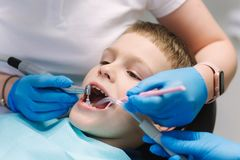 Close up of dentist examination little boy`s teeth in clinic stock photo