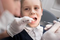 Pediatric dentist examining teeth of boy patient in dental clinic using dental tools - probe and mirror. Close-up dentist examining teeth of boy patient in Royalty Free Stock Image