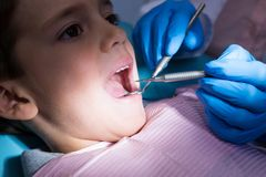 Dentist giving dental treatment to boy at clinic Stock Images