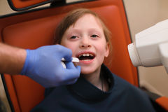 Close up of dentist putting intraoral shield to children patient mouth and assistant directing x-ray machine at dental clinic Stock Photos
