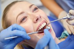 Close up of dentist treating female patient teeth Royalty Free Stock Images