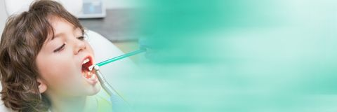 Close up of dentist working on boy's mouth and blurry teal transition Stock Photo