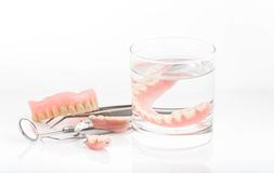 Close up of dentures in glass of water and dental hygienist mirror Stock Photography