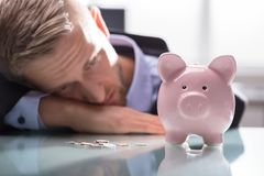 Depressed Man Looking At Coins And Piggybank stock photo