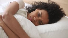 Depressed african woman lying on bed embraces pillow feels unhappy