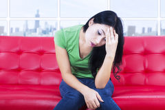 Close-up depressed woman on red sofa indoor Royalty Free Stock Photography