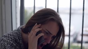 Depressed woman sitting by the window with rain. Close-up of depressed woman is talking over the mobile phone, yelling and crying sitting on the floor by the stock video footage