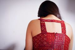 Close up of a depressed woman, wearing a red blouse with her head down after being raped and suffering sexual abuse, in. A white background Royalty Free Stock Photo