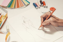 Close-up of designer drawing a fashion sketch.  royalty free stock image