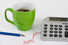 Close-up of a desk with a coffee cup, pen, a calcu. Lator and a balance sheet bend Stock Images