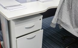 Desk drawer and office desk with jacket on chair royalty free stock photo