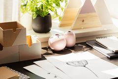 Close-up on desk with drawings and wooden boxes in workspace interior with plant. Real photo stock photo
