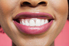 Close-up detail of an African American woman smiling over colored background Stock Photography