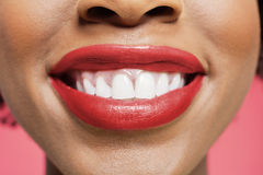 Close-up detail of an African American woman smiling over colored background Stock Photo