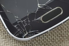Close-up detail of black old cellphone with cracked screen on light cloth background. Gadget repair and maintenance concept.  royalty free stock photos