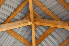 Close-up detail bottom view from inside of bright yellow wooden timber frame and gray metal tiling of alcove roof . Building, cons royalty free stock images