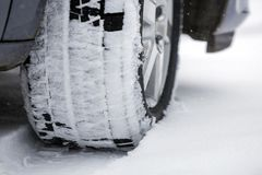 Close up detail car wheel with new black rubber tire protector on winter snow covered road. Transportation and safety concept.  stock photos