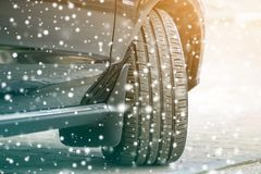 Close up detail car wheel with new black rubber tire protector on winter snow covered road. Transportation and safety concept.  royalty free stock photo