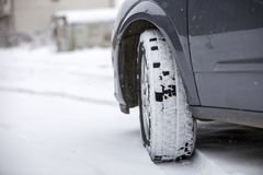 Close up detail car wheel with new black rubber tire protector on winter snow covered road. Transportation and safety concept.  stock photo