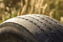 Close-up detail of car wheel tire badly worn and bald because of poor tracking or alignment of the wheels. Royalty Free Stock Photos