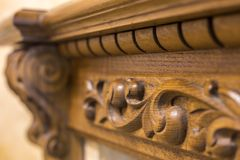 Close-up detail of carved wooden decorative piece of furniture with floral ornament made of natural hardwood. Art craft and design. Concept royalty free stock image