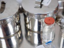 Glass vial next to steel dressing jars Royalty Free Stock Images