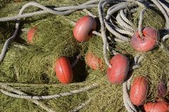 A close up detail of fishing nets, orange floats and rope Royalty Free Stock Photo