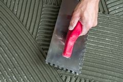 Close-up detail of floor tiles installation. Home improvement, r. Enovation. Workers hand with notched float for tile. Ceramic tile floor adhesive, mortar stock photography