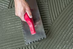 Close-up detail of floor tiles installation. Home improvement, r Royalty Free Stock Photography